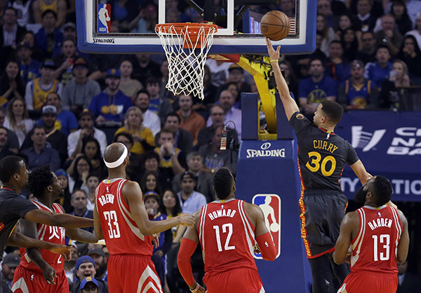 From left, Houston Rockets Patrick Beverley (2), Corey Brewer (33) Dwight Howard (12) and James Harden, right, watch as Golden State Warriors' Stephen Curry (30) lays up a shot during the first half of an NBA basketball game Tuesday, Feb. 9, 2016, in Oakland, Calif. | AP Photo/Ben Margot