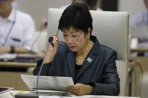 Tokyo Gov. Yuriko Koike looks over a report during an expert panel at the Tokyo Metropolitan government office in Tokyo Thursday, Sept. 29, 2016. The panel, launched by Koike raised concerns about ever-growing unofficial cost estimates and burden on the city and its taxpayers, warned that total cost for the Tokyo 2020 Olympic could exceed 3 trillion yen ($30 billion) unless they take drastic cost-cutting measures.   Shizuo Kambayashi/AP