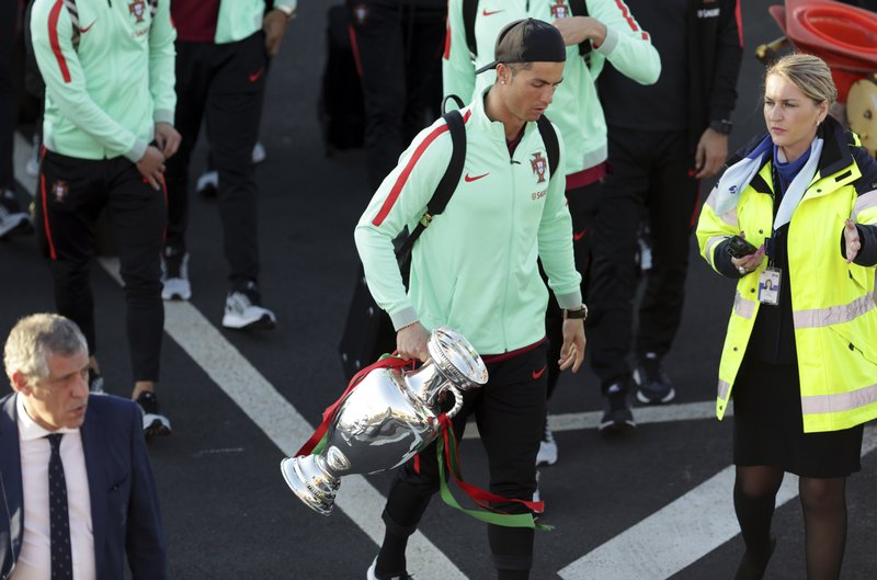 Portugal's Cristiano Ronaldo carries the Euro 2016 European soccer championship trophy as the Portugal team arrives at the Madeira airport outside Funchal, the capital of Madeira island, Portugal, Monday, March 27 2017. Ronaldo will play in his hometown of Funchal Tuesday when Portugal faces Sweden in a friendly soccer match (Wednesday in Manila). | AP Photo/Armando Franca