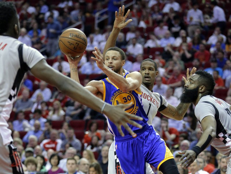Golden State Warriors' Stephen Curry dishes the ball between Houston Rockets' Clint Capela, Trevor Ariza and James Harden in the first half of an NBA basketball game in Houston, Tuesday, March 28, 2017 (Wednesday in Manila). | AP Photo/Michael Wyke