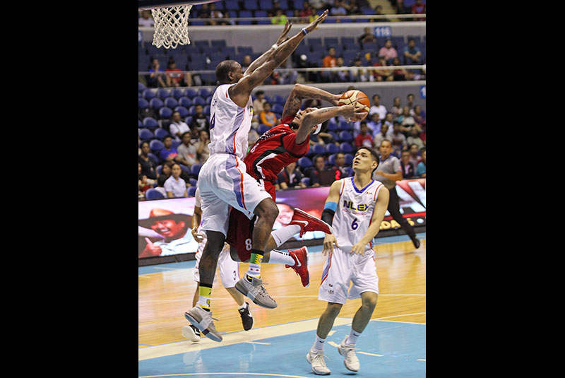 Alaska's Calvin Abueva (right) suspends himself in the air while trying to defy NLEX's Wayne Chism's defense during their PBA Commissioner's Cup clash at the Smart Araneta Coliseum. JUN MENDOZA