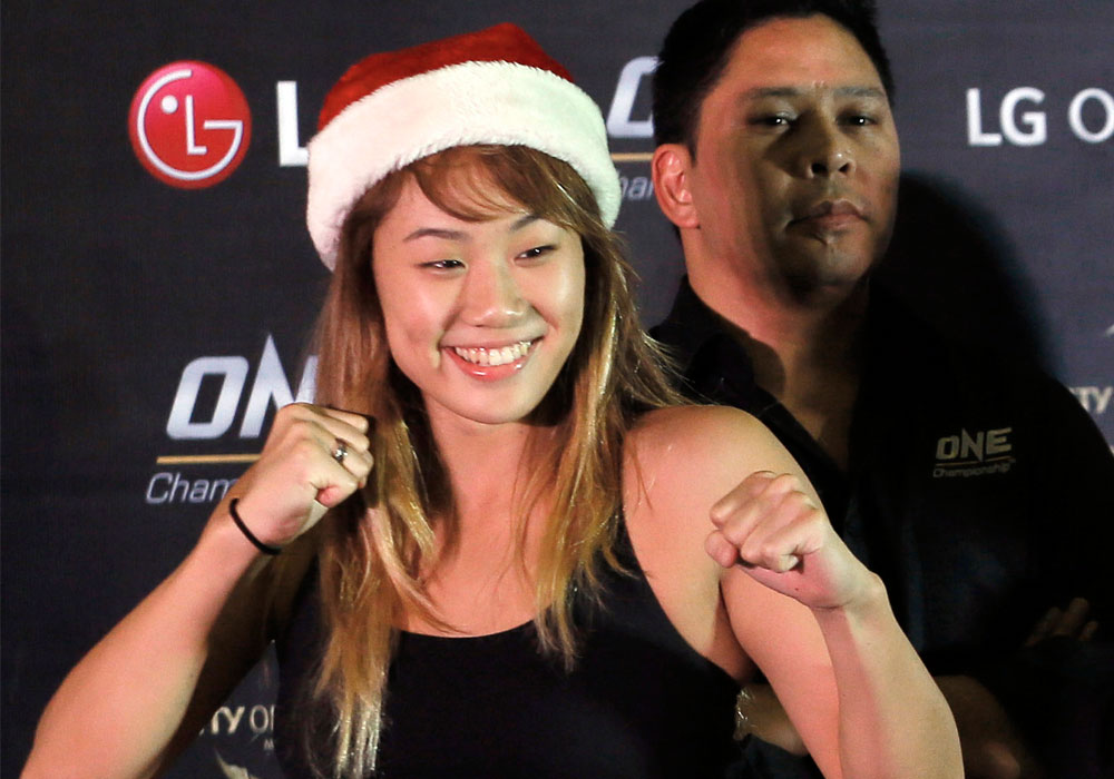 In this Dec. 10, 2015, file photo, mixed martial arts fighter Angela Lee, of Singapore, poses wearing a Santa hat, following a weigh-in ceremony for her One Championship bout, at the Mall of Asia Arena at suburban Pasay city south of Manila, Philippines. | AP Photo/Bullit Marquez, File