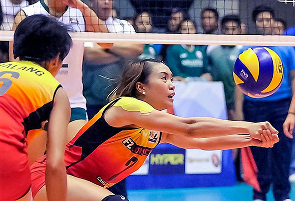 Aby Marano of F2 Logistics saves the ball as teammate Ara Galang looks on.