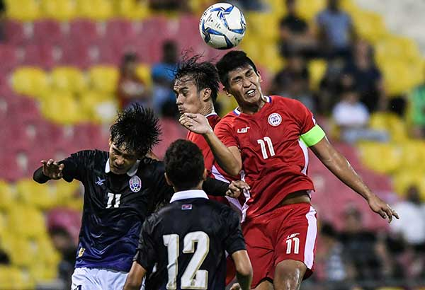 The Philippines' Julian Mariano Clarino heads the ball past teammate Reymart Cubon and  two Cambodian defenders during their men's football Group B round match at the 29th Southeast Asian Games at Selayang Stadium, outside Kuala Lumpur. AFP