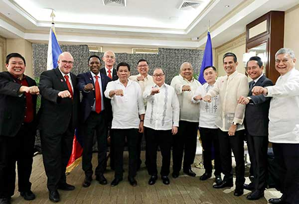 President Duterte, center, does the 'fist pose' with FIBA officials during a courtesy call at Malacañang Thursday night. Joining the President are Manny V. Pangilinan, chairman emeritus of the Samahang Basketbol ng Pilipinas, Executive Secretary Salvador Medialdea, Philippine Sports Commission chairman William Ramirez and Special Assistant to the President Christopher Lawrence Go, SBP executive director Sonny Barrios, MVP Group top executive Mike Toledo, SBP president Al Panlilio and SBP official Butch Antonio. RICHARD MADELO/MALACAÑANG PHOTO