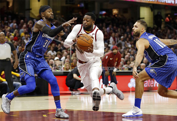 Cleveland Cavaliers' Dwyane Wade, center, drives to the basket between Orlando Magic's Terrence Ross, left, and Evan Fournier, from France, in the first half of an NBA basketball game, Saturday, Oct. 21, 2017, in Cleveland. | AP Photo/Tony Dejak