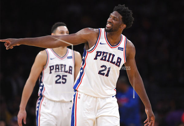 Philadelphia 76ers center Joel Embiid, right, gestures toward actor Kevin Hart after scoring as guard Ben Simmons stands in the background during the second half of an NBA basketball game against the Los Angeles Lakers, Wednesday, Nov. 15, 2017, in Los Angeles. The 76ers won 115-109. | AP Photo/Mark J. Terrill