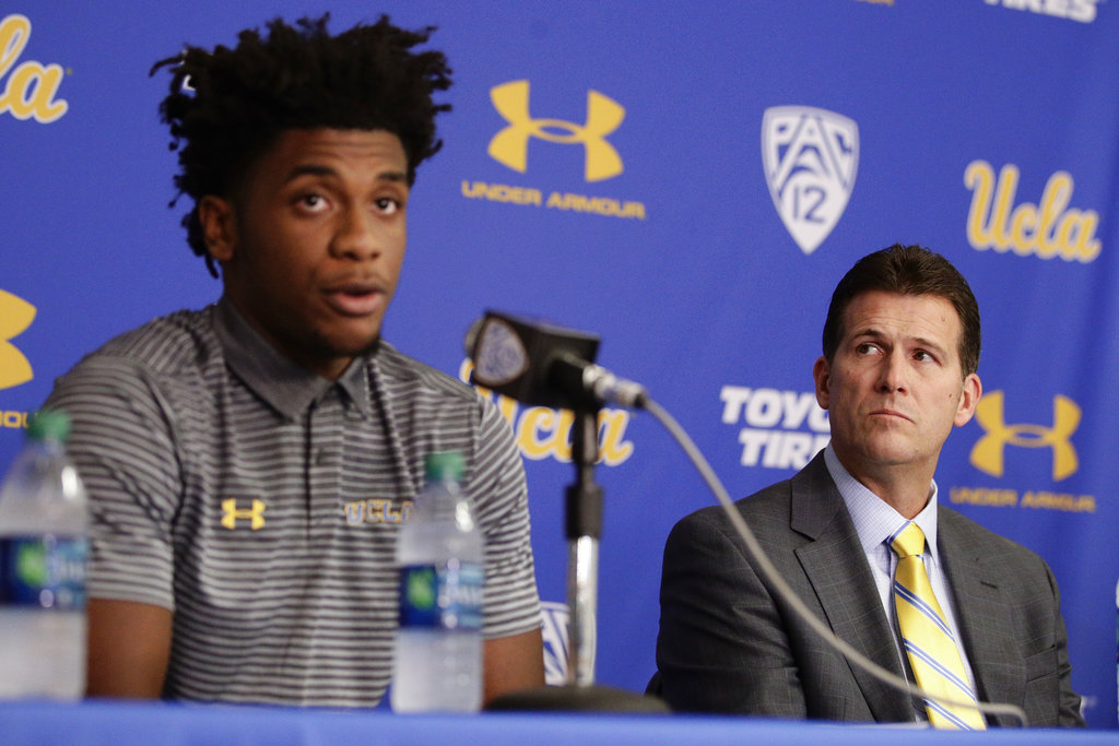 UCLA head coach Steve Alford, right, listens as Jalen Hill reads his statement during a news conference at UCLA Wednesday, Nov. 15, 2017, in Los Angeles. Three UCLA NCAA college basketball players accused of shoplifting in China admitted to the crime and apologized before coach Steve Alford announced they were being suspended indefinitely. | AP Photo/Jae C. Hong