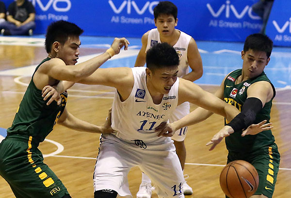Ateneo Blue Eagles' Isaac Go prevents FEU Tamaraws Barkley Eboña (left) and Alejandro Inigo from getting near the ball as he himself is being shackled during their semifinal match yesterday at the Smart Araneta Coliseum. | Miguel De Guzman