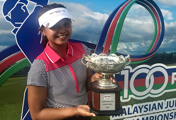 Mikhaela Fortuna holds her trophy after completing her come-from-behind win in the Malaysian Junior Open Championship.