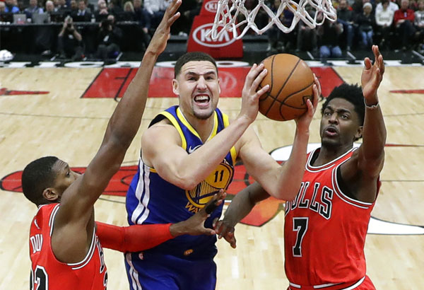 Golden State Warriors' Klay Thompson (11) shoots between Chicago Bulls' Kris Dunn (32) and Justin Holiday, right, during the second half of an NBA basketball game Wednesday, Jan. 17, 2018, in Chicago. | AP Photo/Charles Rex Arbogast