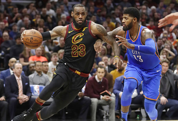 Cleveland Cavaliers' LeBron James (23) drives against Oklahoma City Thunder's Paul George (13) in the first half of an NBA basketball game, Saturday, Jan. 20, 2018, in Cleveland. | AP Photo/Tony Dejak