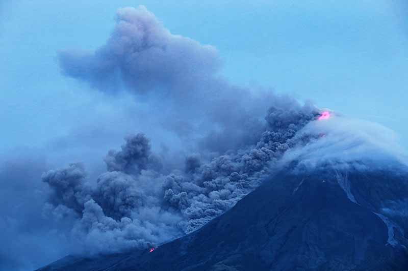 "Cloud-covered Mayon volcano spews ash as it erupts near the Philippine city of Legazpi in Albay province, early on January 16, 2018. Thousands fled from their homes as lava oozed out of a rumbling Philippine volcano on January 15 in what volcanologists described as a ""quiet eruption"", warning it could lead to a hazardous explosion within days. AFP/Charism Sayat"