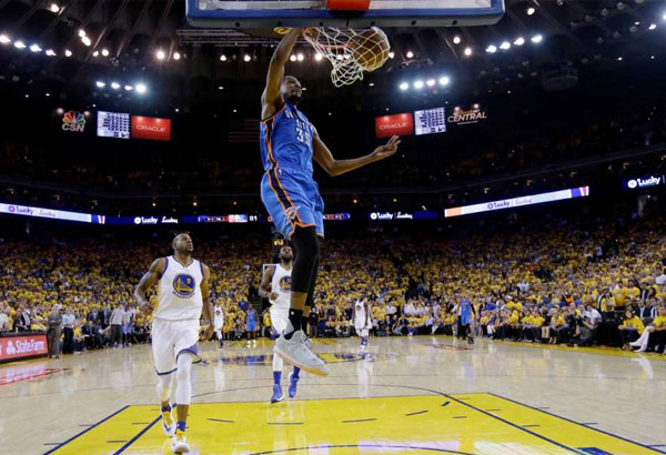 Oklahoma City Thunder's Kevin Durant (35) dunks past Golden State Warriors' Andre Iguodala (9) during the second half in Game 5 of the NBA basketball Western Conference finals Thursday, May 26, 2016, in Oakland, Calif. Golden State won 120-111. AP/Marcio Jose Sanchez