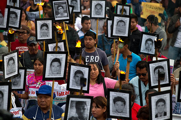 In this April 26, 2016 file photo, family members and supporters of 43 missing teachers college students carry pictures of the students as they march to demand the case not be closed and that experts' recommendations about new leads be followed, in Mexico City. In Mexico's ten year war on drugs advances can be seen in places like the violent border city of Ciudad Juarez, where the number of homicides fell when it began a stepped-up policing effort. But those kind of gains haven't been seen in most other states. AP Photo/Rebecca Blackwell, File