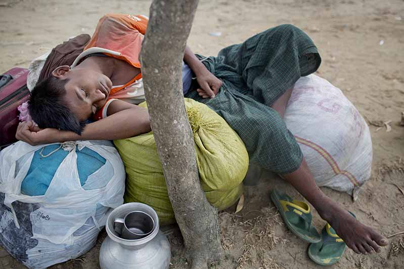 """A Rohingya Muslim, who crossed over from Myanmar into Bangladesh recently, sleeps on his belongings as he waits for permission to proceed towards a refugee camp near Shah Porir Dwip, Bangladesh, Thursday, Nov. 16, 2017. Hundreds of thousands of Rohingya have fled Myanmar's Rakhine state since late August, when the military launched what they called """"clearance operations"""" in response to insurgent attacks. The refugees say soldiers and Buddhist mobs attacked them and burned their villages to force them to flee. AP/A.M. Ahad"""