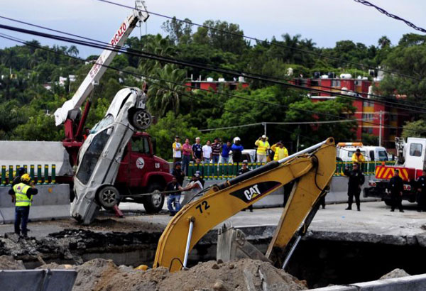 "FILE - In this July 12, 2017 file photo, rescue workers use a crane to lift a vehicle that drove into a sinkhole on a highway in Cuernavaca, Mexico, where a father and son were killed when the deep sinkhole swallowed their car. The highway connecting Mexico City and the Pacific coast resort of Acapulco had only recently been redone and was still festooned with inaugural banners proclaiming, ""Thank you, Mr. President!"" for the project. (AP Photo/Tony Rivera, File)"