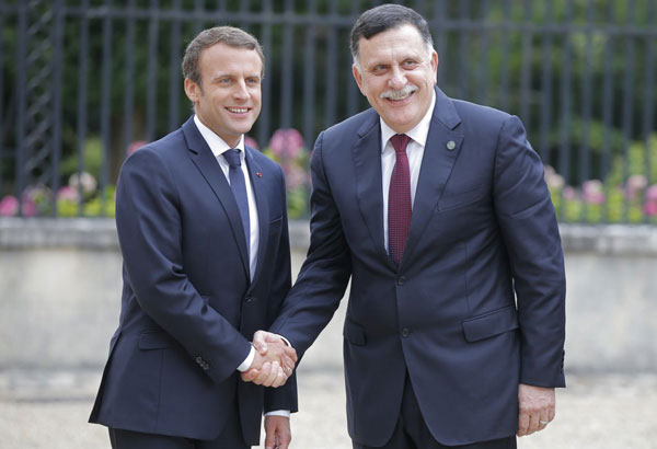France's President Emmanuel Macron, left, welcomes Libya's Prime Minister Fayez al-Sarraj of the U.N.-backed government at the Chateau of the La Celle-Saint-Cloud, west of Paris, France, Tuesday, July 25, 2017. President Emmanuel Macron is hosting a meeting of the two main rival leaders of chaotic Libya, trying to play peacemaker in a country where the stakes are high for both Europe and Africa. (AP Photo/Michel Euler)