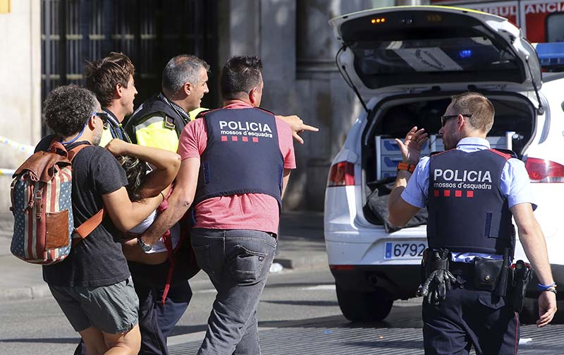 An injured person is carried in Barcelona, Spain, Thursday, Aug. 17, 2017, after a white van jumped the sidewalk in the historic Las Ramblas district, crashing into a summer crowd of residents and tourists and injuring several people, police said. AP/Oriol Duran, file
