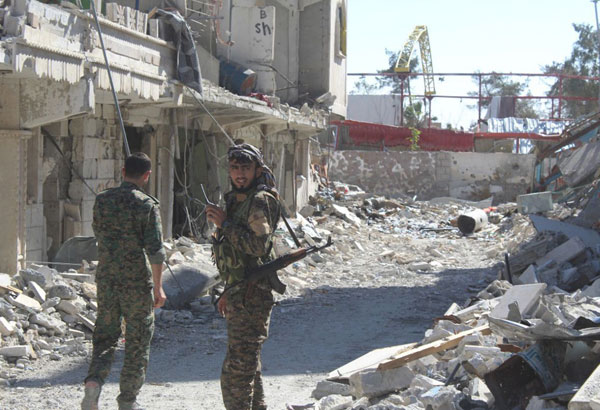 In this picture taken on Monday Oct. 16, 2017 and provided by The Syrian Democratic Forces (SDF), a U.S.-backed Syrian Kurdish forces outlet that is consistent with independent AP reporting, shows Syrian Democratic Forces (SDF) fighters, stand on destroyed street where they battle against the Islamic State militants, in Raqqa, Syria. The U.S-backed Syrian forces battling the Islamic State group in Syria say Raqqa's national hospital, one of the militants' last holdouts in city has been captured. (Syrian Democratic Forces via AP)