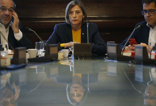 President of the Catalan parliament Carme Forcadell, center, gathers to discuss with parliament representatives their next move after Spanish government announced plans to remove members of the region's pro-independence government, at the Catalonia Parliament, in Barcelona, Spain, Monday, Oct. 23, 2017. Rajoy has called on Spain's Senate to trigger a section of the constitution that allows the central government to temporarily govern a region if its leaders break the law. (AP Photo/Manu Fernandez)