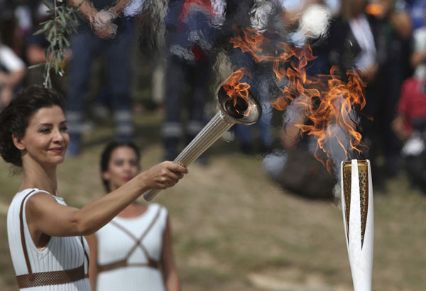 Actress Katerina Lehou as high priestess, passes the Olympic Flame onto a Pyeongchang torch bearer after it was lit from the sun's rays, during the final dress rehearsal for the lighting of the Olympic flame at Ancient Olympia, southwestern Greece on Monday, Oct. 23, 2017. The flame will be transported by torch relay to Pyeongchang, South Korea, which will host the Feb. 9-25, 2018 Winter Olympics. (AP Photo/Petros Giannakouris)
