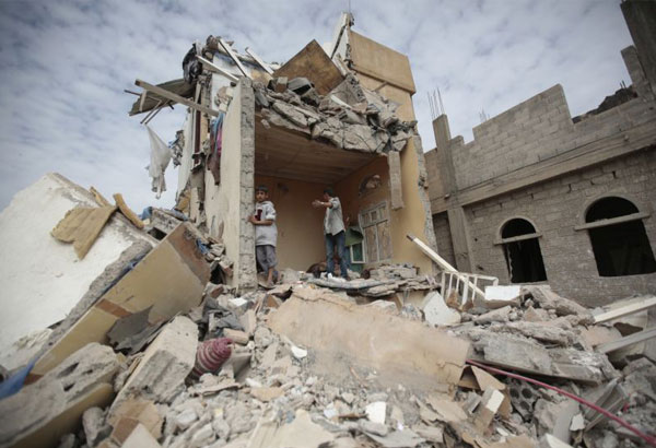 """FILE - In this Aug. 25, 2017 file photo, boys stand on the rubble of a house destroyed by Saudi-led airstrikes in Sanaa, Yemen. The Saudi-led coalition fighting in Yemen is blaming a rebel missile launch on Iran and warning it could be """"considered as an act of war."""" Early Monday, Nov. 6, 2017, the coalition also closed off the land, sea and air ports to the Arab world's poorest country over the missile launch targeting Riyadh. (AP Photo/Hani Mohammed, File)"""