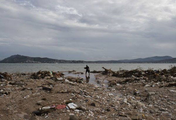 A man collects wood from a flooded beach in Nea Peramos west of Athens, on Friday, Nov. 17, 2017. Greece's fire department says two more people have been reported missing after deadly flash flooding west of Athens that has already confirmed to have killed at least 16 people. (AP Photo/Petros Giannakouris)