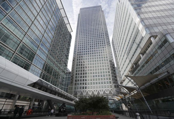 FILE - In this July 28, 2017 file photo, is One Canada Square house, center, that hosts the offices of the European Banking Authority EBA, headquarters in London. Brexit is still well over year away but two cities on Monday, Nov. 20, 2017 will already be celebrating Britain's departure from the European Union. Two major EU agencies currently in London will be given a new home to move to and the two prizes are hotly fought over by most of the other 27 nations. (AP Photo/Frank Augstein, File)