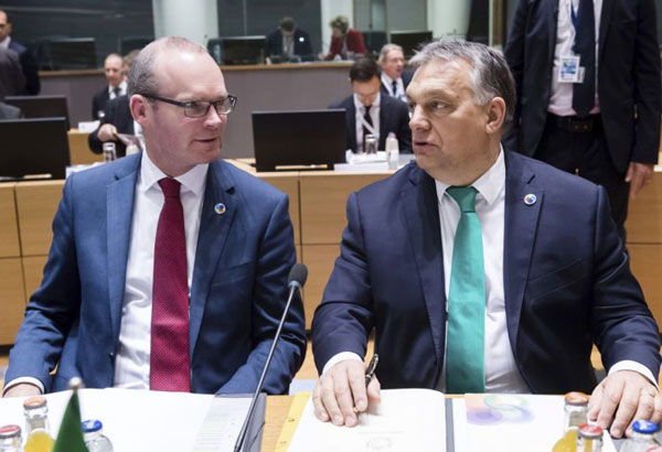 Hungarian Prime Minister Viktor Orban, right, speaks with Irish Foreign Minister Simon Coveney during a round table meeting at an Eastern Partnership Summit in Brussels, Friday, Nov. 24, 2017. European Union leaders meet with their counterparts from Armenia, Azerbaijan, Belarus, Georgia, Moldova and Ukraine for a summit in Brussels on Friday. British Prime Minister Theresa May is also due to hold separate talks with her EU partners. (AP Photo/Geert Vanden Wijngaert)