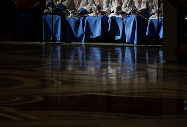 FILE - In this Nov. 13, 2016 file photo shows altar boys holding their booklets of prayers as they wait for the start of a Mass celebrated by Pope Francis on the occasion of the homeless jubilee, inside St. Peter's Basilica, at the Vatican. Catholic officials in Italy have threatened former altar boys of the pope with criminal defamation charges for having publicly accused an older seminarian of sexual misconduct when they lived together at the youth seminary inside the Vatican gardens. (AP Photo/Gregorio Borgia, files)