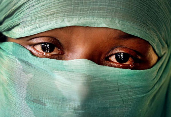 In this Wednesday, Nov. 22, 2017, photo, F, 22, who says she was raped by members of Myanmar's armed forces in June and again in September, cries as she speaks to The Associated Press in her tent in Kutupalong refugee camp in Bangladesh. The Associated Press has found that the rape of Rohingya women by Myanmar's security forces has been sweeping and methodical. The AP interviewed 29 women and girls who say they were raped by Myanmar's armed forces, and found distinct patterns in their accounts, their assailants' uniforms and the details of the rapes themselves. The most common attack involved groups of soldiers storming into a house, beating any children inside and then beating and gang raping the women. (AP Photo/Wong Maye-E)