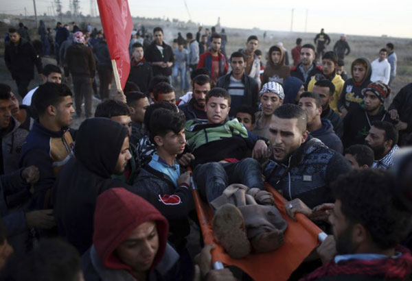 Palestinians evacuate an injured protester during clashes on the Israeli border with Gaza, Monday, Dec. 11, 2017. (AP Photo/ Khalil Hamra)