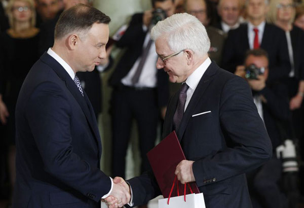 Poland's President Andrzej Duda, left, takes the oath from new Foreign Minister Jacek Czaputowicz in the government of Prime Minister Mateusz Morawiecki at the Presidential Palace in Warsaw, Poland, Tuesday, Jan. 9, 2018, just hours before Morawiecki heads off to Brussels for talks with top European Union officials. (AP Photo/Czarek Sokolowski)