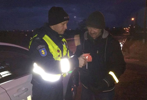 In this Sat, Jan. 6, 2018 photo provided by the Lithuania Police, a policeman gives a road user a candle, in an undisclosed town in Lithuania. Pedestrians and cyclists, who do not wear mandatory reflectors and are almost invisible during in the dark months, risk a 140 euro ($168) fine in Lithuania. But now they also can get a candle on top of the ticket. (Lithuania Police via AP)