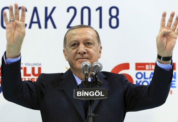 Turkey's President Recep Tayyip Erdogan gestures to supporters of his ruling Justice and Development Party (AKP), at a rally in Bingol, eastern Turkey, Saturday, Jan. 13, 2018. Erdogan has said Turkey will oust Kurdish militants from Afrin, northern Syria, as the military shelled the area from across the border. Turkey considers the YPG a terror group and an extension of the Kurdish insurgency within its own borders. (Pool Photo via AP)