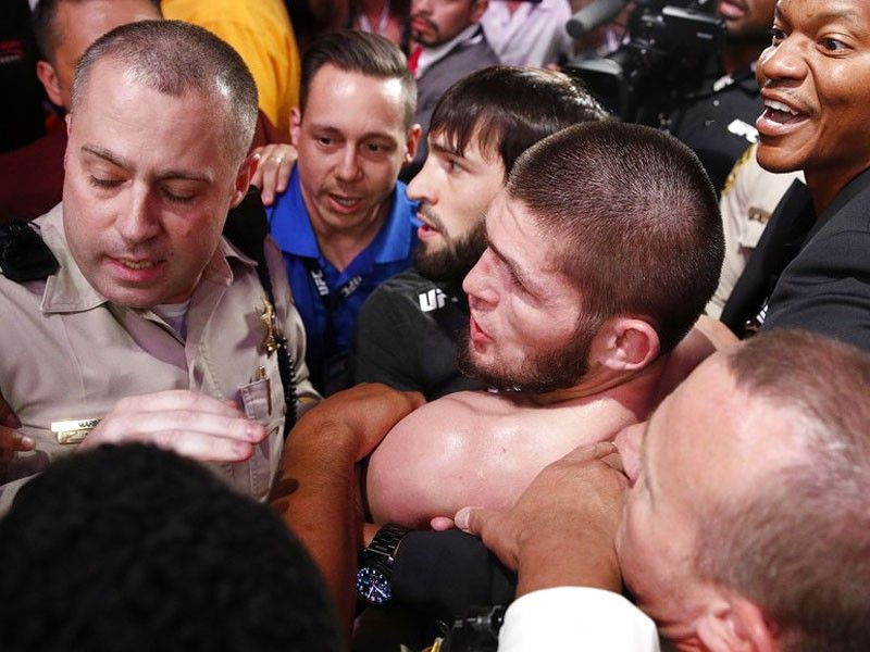 Khabib Nurmagomedov, bottom center, is held back outside of the cage after fighting Conor McGregor in a lightweight title mixed martial arts bout at UFC 229 in Las Vegas, Saturday, Oct. 6, 2018. Nurmagomedov won the fight by submission during the fourth round to retain the title.