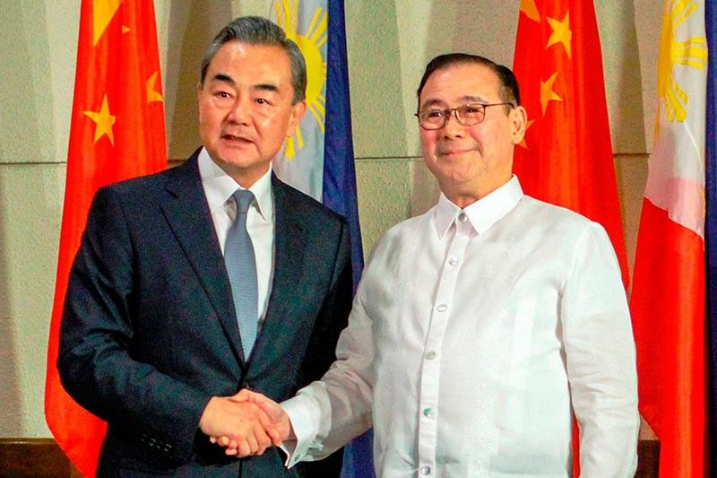 Foreign Affairs Secretary Teodoro Locsin Jr., right, and visiting Chinese Foreign Minister Wang Yi shake hands during the latter's courtesy call in Davao city, southern Philippines Monday, Oct. 29, 2018.