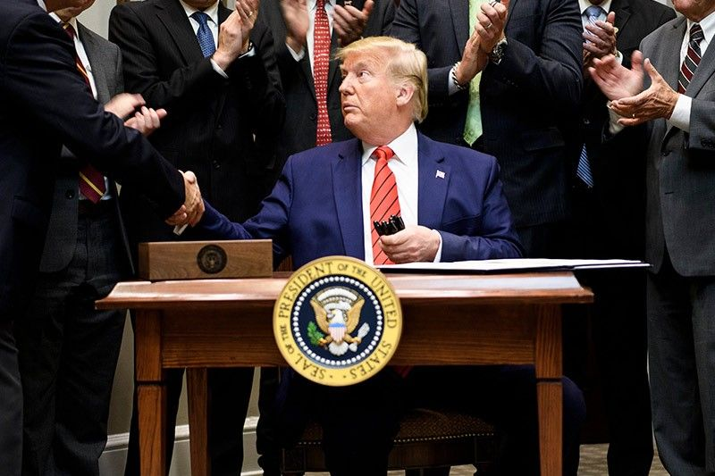 US President Donald Trump shakes hands after signing an executive order regarding federal regulations in the Roosevelt Room of the White House October 9, 2019, in Washington, DC. Brendan Smialowski/AFP