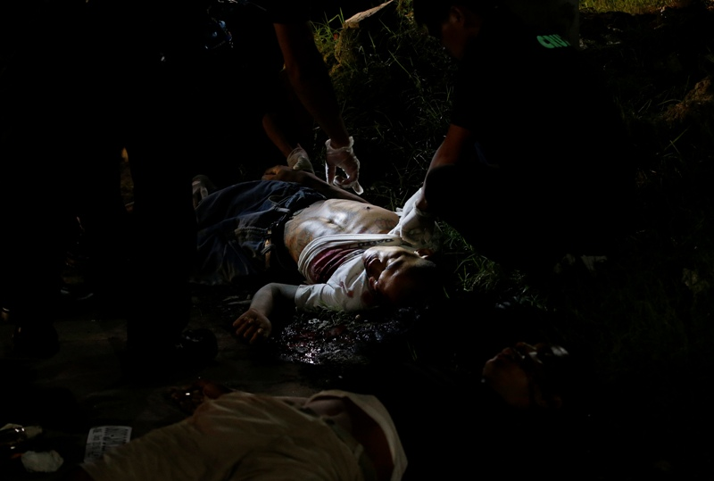 In this Sept. 6, 2016 photo, police inspect one of two unidentified drug suspects after being shot by police as they tried to evade a checkpoint in Quezon city, north of Manila, Philippines. Bodies had begun turning up in cities all over the Philippines ever since President Rodrigo Duterte launched a controversial war on drugs this year. Drug dealers and drug addicts, were being shot by police or slain by unidentified gunmen in mysterious, gangland-style murders that were taking place at night. AP/Aaron Favila, File