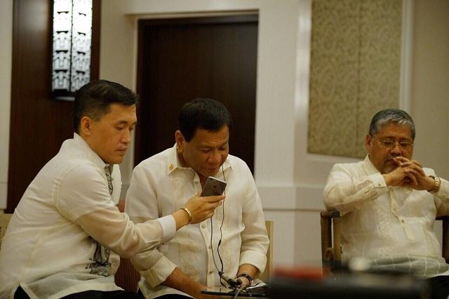 "President Duterte talks to US President Trump on the phone while acting Foreign Affairs Secretary Manalo listens in.Photo courtesy of Secretary Christopher ""Bong"" Go"