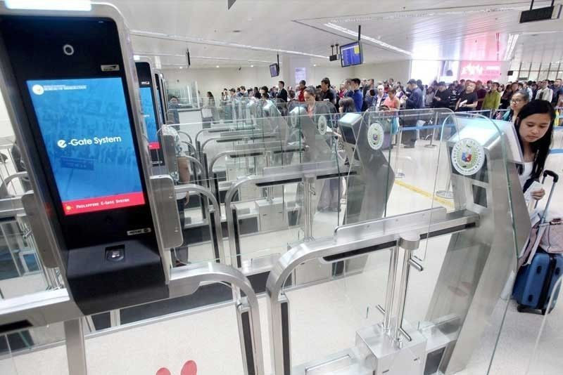 A passenger uses the electronic gate or e-gate at a Ninoy Aquino International Airport terminal that can process a machine-readable passport within eight to 15 seconds while others form long lines to pass through immigration officers.