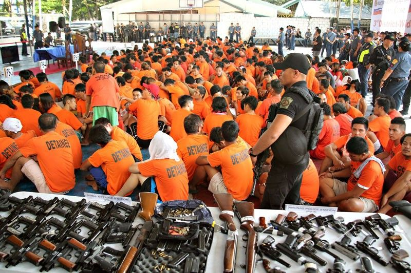 Police officers carrying high-powered firearms guard 19,209 detainees at Camp Karingal in Quezon City yesterday. The detainees were rounded up during a citywide anti-crime drive that started on Jan. 13 and ended yesterday.