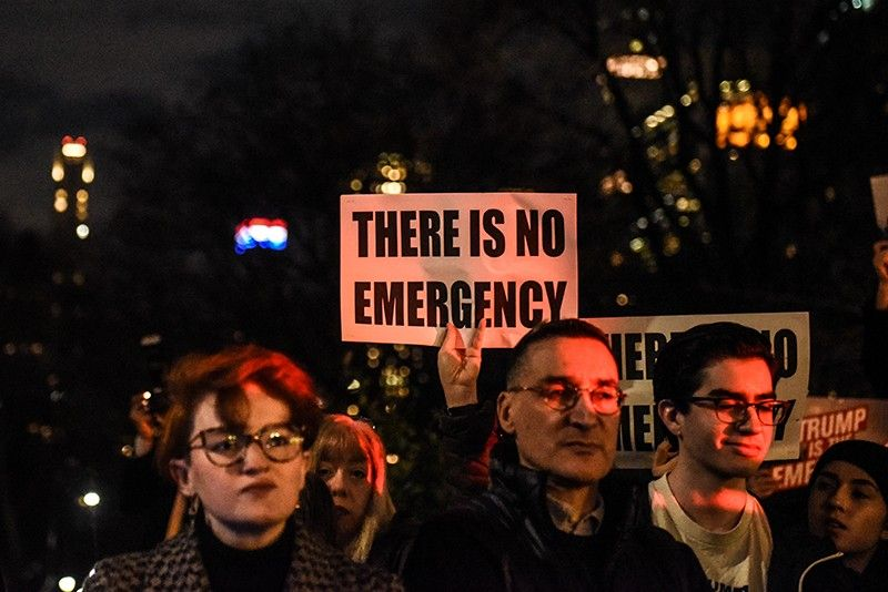 People hold protest signs in front of Trump International Hotel on February 15, 2019 in New York City. The group is protesting U.S. President Donald Trump's declaration of a National Emergency in order to build his proposed border wall.