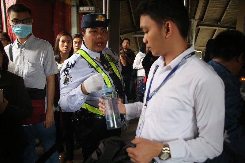 Sinisita ng isang gwardya ang mga may dalang tubig at kahalintulad na likido sa entrance ng MRT North Avenue station.