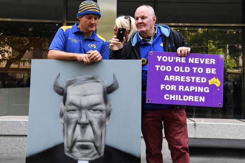 Protesters hold placards outside the County Court to hear the sentencing of Cardinal George Pell in Melbourne on March 13, 2019. Disgraced Australian Cardinal George Pell was sentenced to six years in jail for child sex crimes in a Melbourne court on March 13 with a minimum period of three years and eight months to be served.