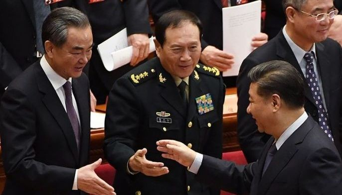 China's President Xi Jinping (R) shakes hands with Foreign Minister Wang Yi (L) and Defence Minister Wei Fenghe as they leave after the closing session of the Chinese People's Political Consultative Conference at the Great Hall of the People in Beijing on March 13, 2019.