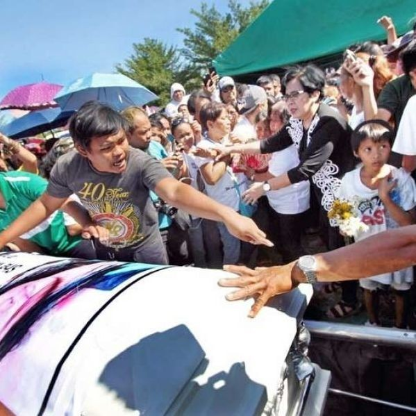 A man holds back the crowd during the burial rites for murdered teenager Christine Lee Silawan at the Catleya Memorial Garden in Cordova, Cebu yesterday.