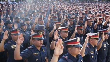 Newly promoted police officers take their oath at the NCRPO headquarters at Camp Bagong Diwa in Taguig yesterday.