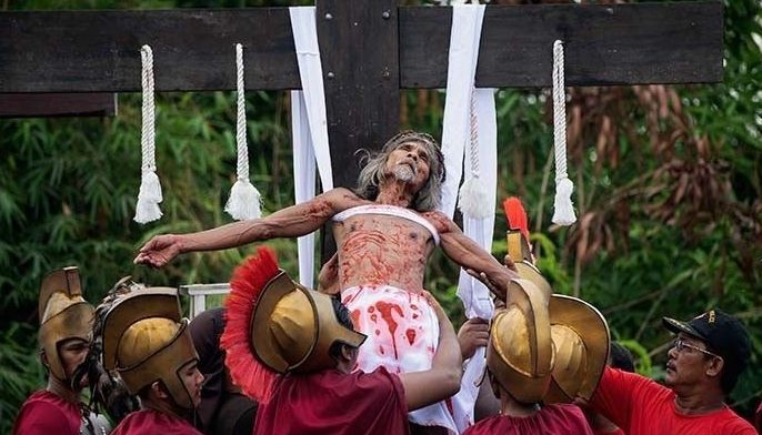 A Philippine Christian devotee is lowered from a cross after being nailed during a reenactment of the Crucifixion of Christ during Good Friday ahead of Easter in San Juan, Pampanga, on April 19, 2019. Hundreds of barefoot men beat themselves with flails and at least 10 were to be nailed onto crosses throughout Good Friday in a blood-soaked worship display in the Philippines, Asia's Catholic outpost.